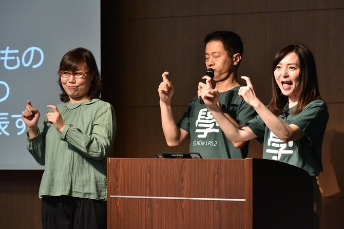写真:「あいさつ」の手話を教えてくれている松森さん、植木さん、手話通訳の方